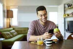 Smiling man using mobile phone while holding apple